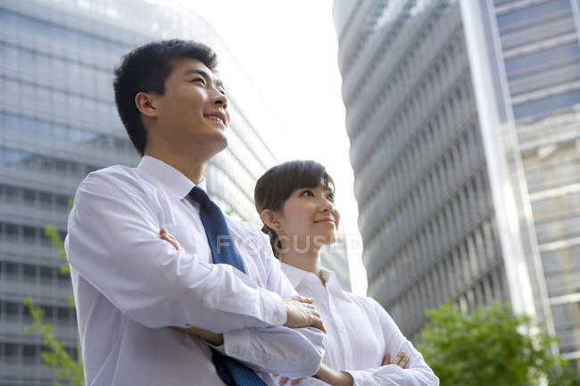 Chinese businessman and businesswoman with arms crossed in front of skyscraper — Stock Photo