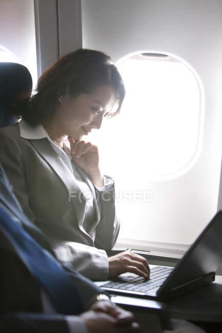Chinese businesswoman using laptop on plane — Stock Photo