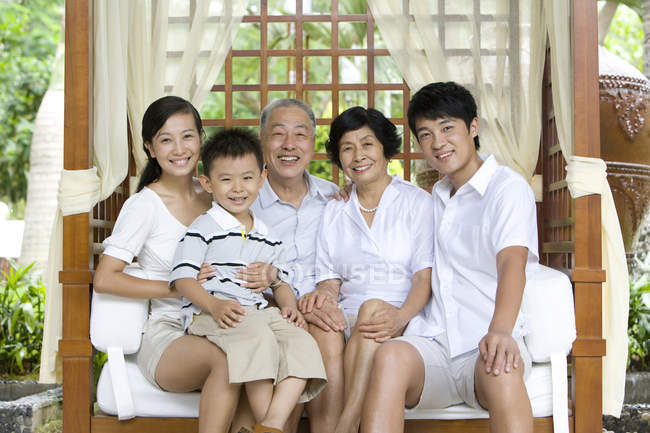 Portrait of Chinese family with boy sitting on bench on vacation — Stock Photo