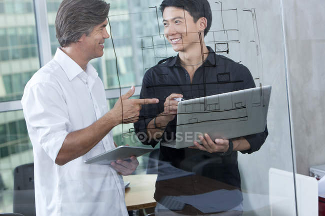 Мужчины дизайнеров с ноутбуком и цифровой планшет в зал Совета — стоковое фото