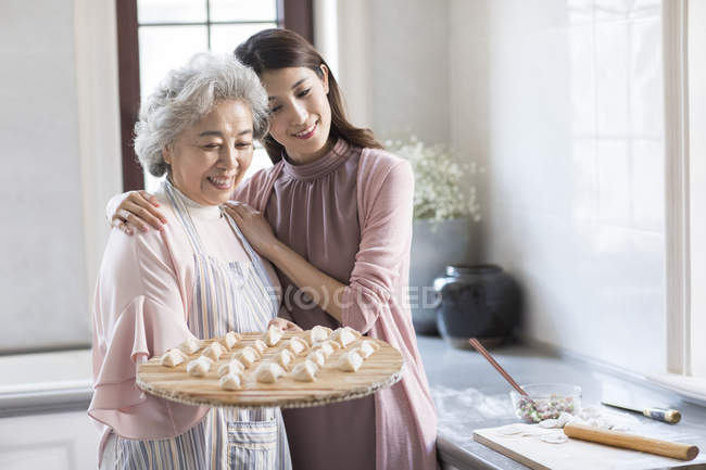 Chinese senior and young women making dumplings in kitchen — Stock Photo