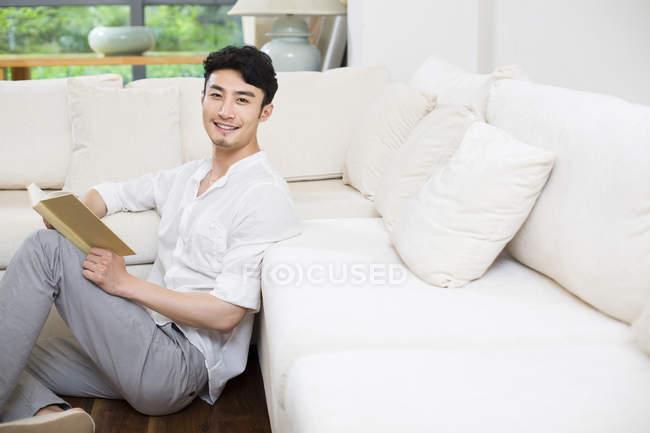 Китаец сидит с книгой на полу в гостиной — стоковое фото