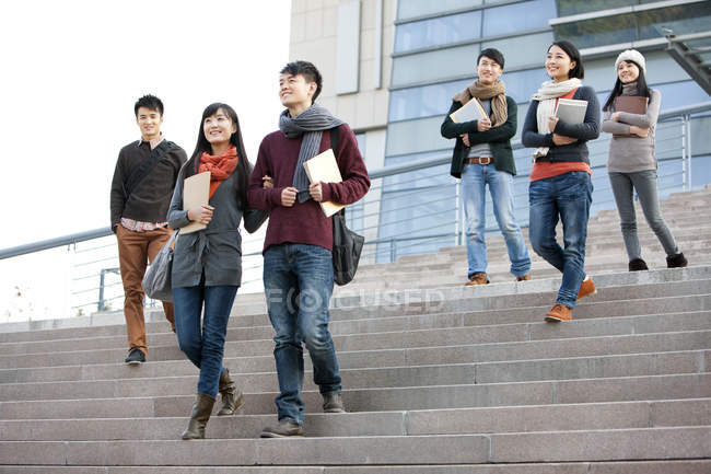 Estudiantes universitarios chinos caminando por los escalones del edificio universitario — Stock Photo