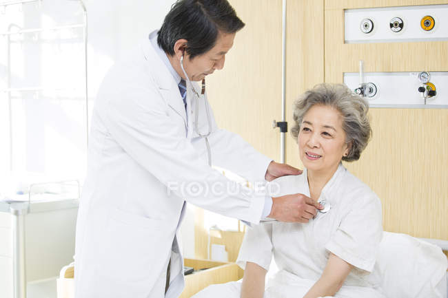Chinese doctor using stethoscope on patient in hospital — Stock Photo