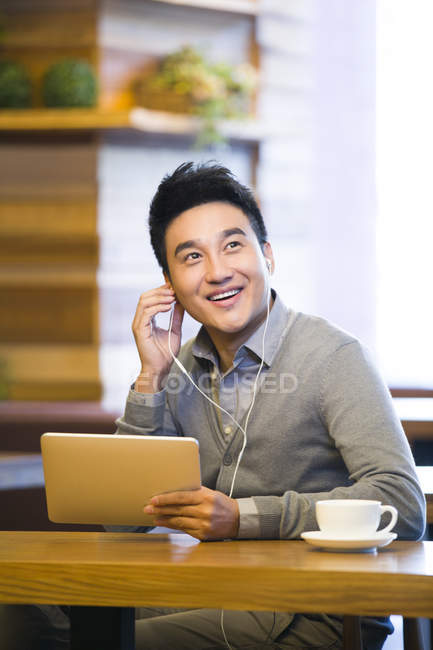 Chinese man listening to music with digital tablet in coffee shop — Stock Photo