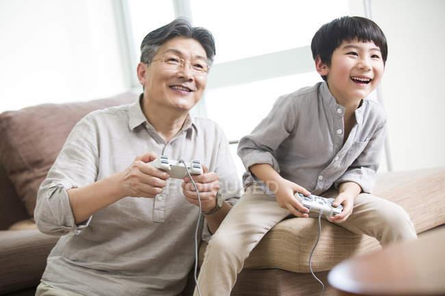 Nonno cinese e nipote che gioca video gioco nel salotto — Foto stock