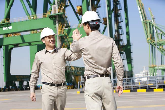 Мужчины, работающие в судоходной промышленности Китая, дают пять — стоковое фото
