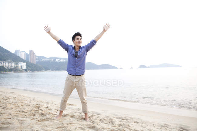 Chinese man with arms outstretched on beach of Repulse Bay, Hong Kong — Stock Photo