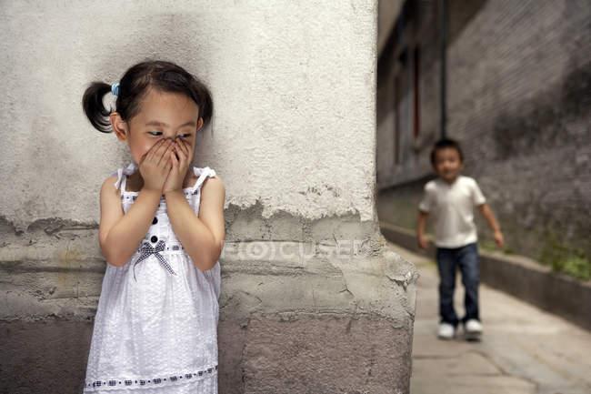 Boca de cobertura menina chinesa enquanto brincava de esconder e procurar — Fotografia de Stock