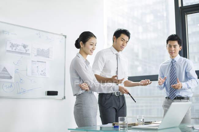 Équipe d'affaires chinoise parlant sur la réunion dans la salle de conseil — Photo de stock
