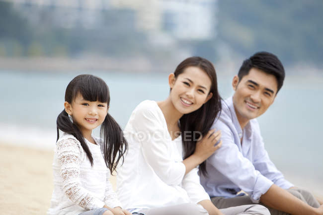 Chinese parents with daughter resting on beach sand and looking in camera — Stock Photo