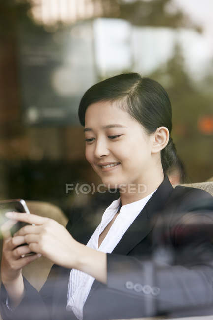 Chinese businesswoman using smartphone in cafe — Stock Photo