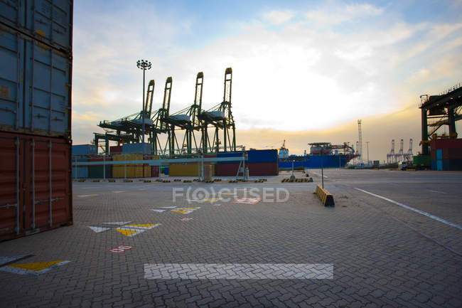 View of cranes, containers and cargo ships at dusk — Stock Photo