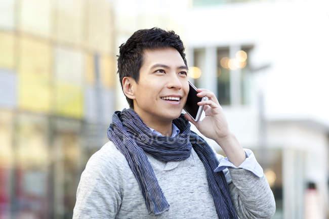 Uomo cinese alla moda che parla su telefono su strada — Foto stock