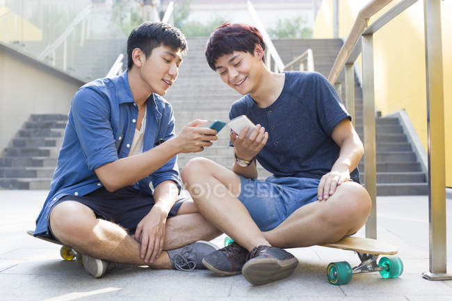 Chinese men sitting on skateboards and looking at smartphones — Stock Photo