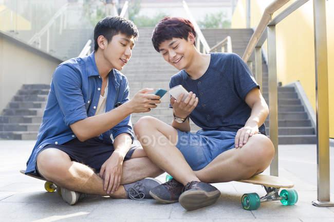 Китайские люди, сидя на скейтбордах и глядя на смартфоны — стоковое фото