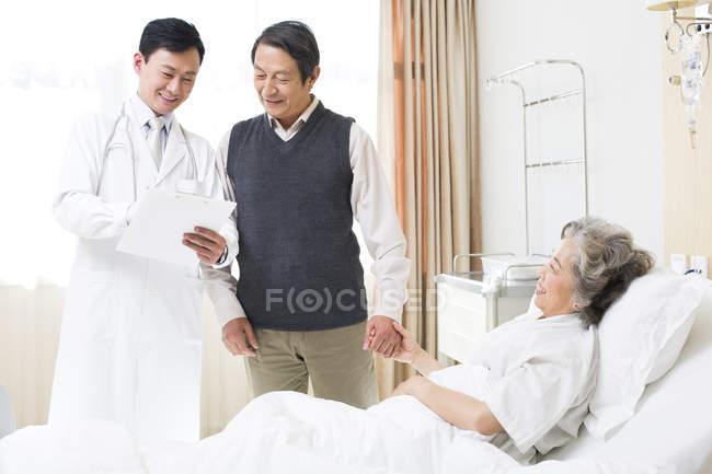 Le docteur chinois debout avec couple de personnes âgées à l'hôpital — Photo de stock