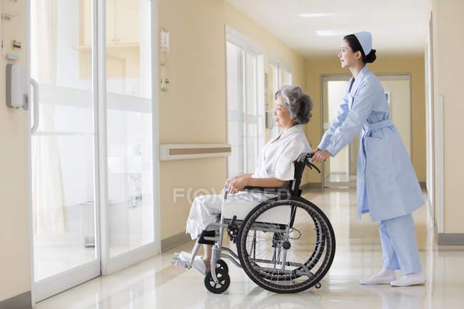 Chinese nurse taking care of senior woman in wheelchair — Stock Photo