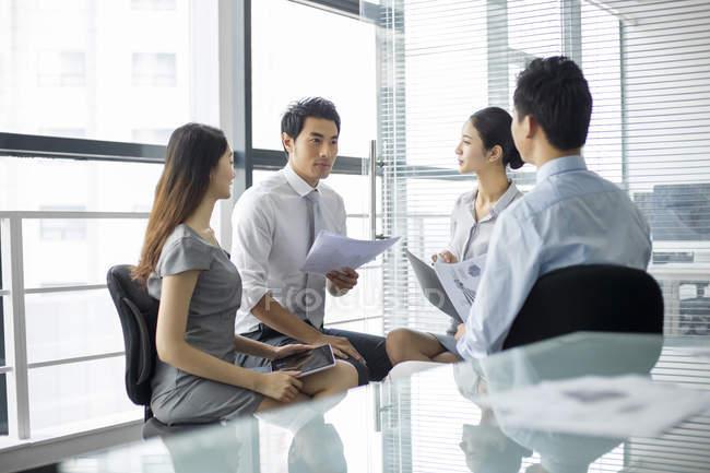 Équipe d'affaires chinoise parlant en réunion — Photo de stock