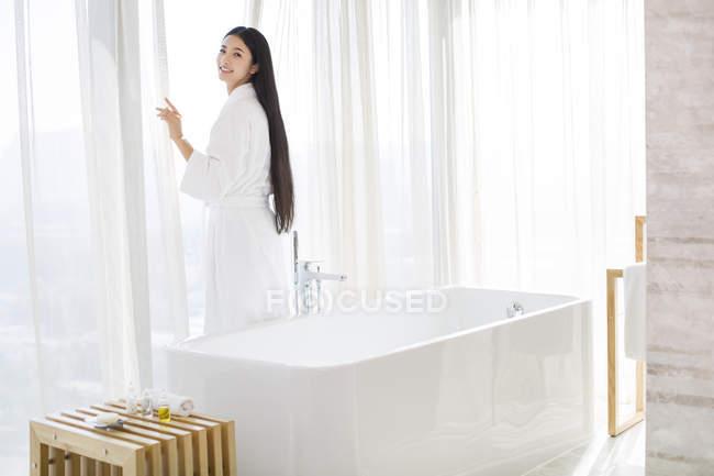 Китаянки в Халат стоя на окно ванной — стоковое фото
