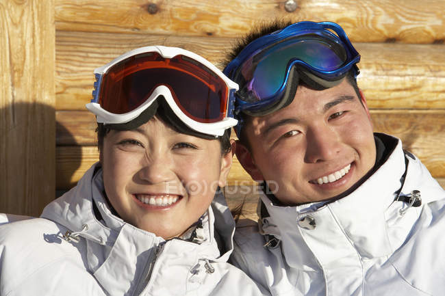 Chinese couple in ski goggles smiling in camera — Stock Photo
