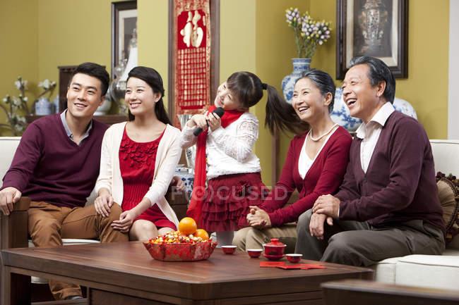 Cheerful family singing karaoke during Chinese New Year — Stock Photo