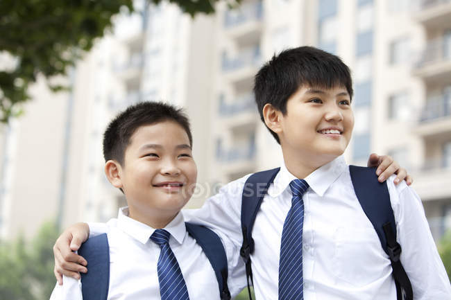 Cheerful classmates in school uniform looking at view — Stock Photo