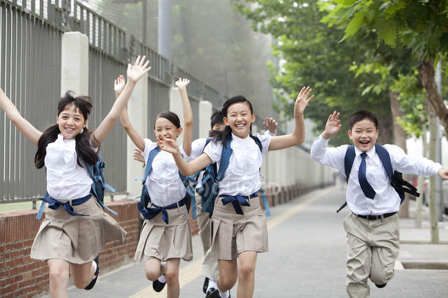 Schoolchildren in school uniform running on sidewalk — Stock Photo