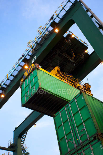 Low angle view of crane and cargo containers at shipping port — Stock Photo