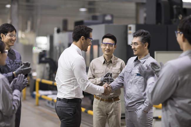 Homme d'affaires et équipe d'ingénieurs serrant la main dans l'usine — Photo de stock