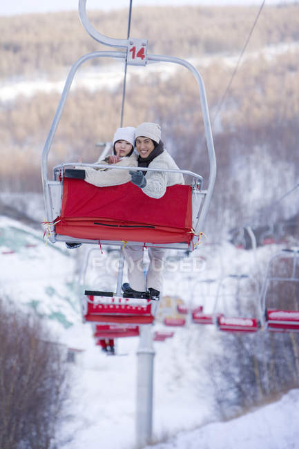 Chinese couple using ski lift at winter resort — Stock Photo