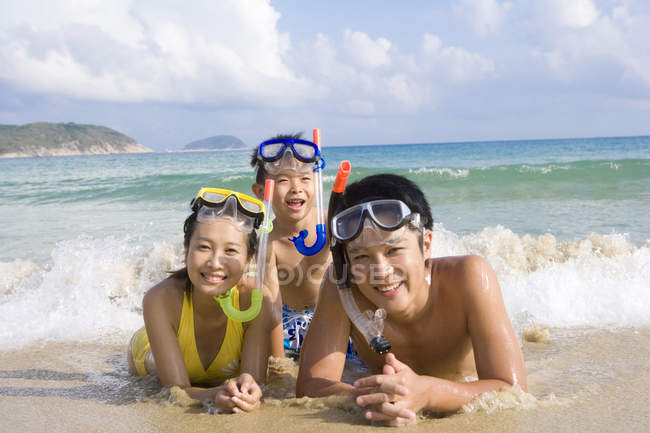 Young family with scuba masks lying on beach — Stock Photo