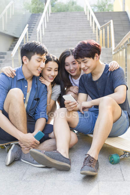 Chinese friends looking at smartphone on stairs with skateboards — Stock Photo