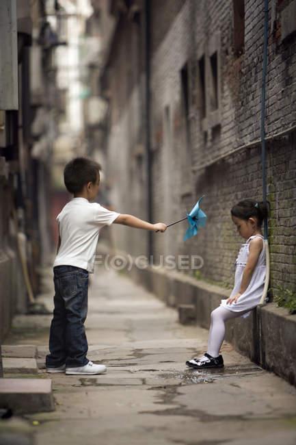 Ragazzo cinese dando triste ragazza carta mulino a vento nel vicolo — Foto stock