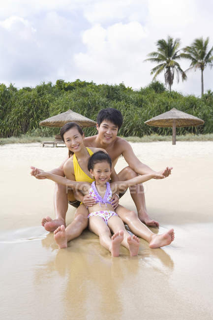 Chinese family with girl with arms outstretched sitting at beach — Stock Photo