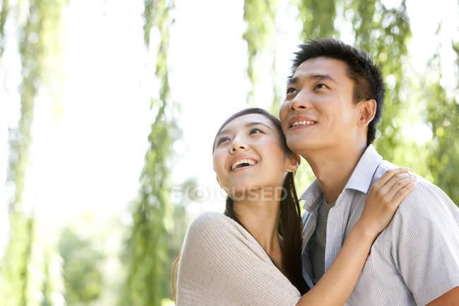 Joven pareja china abrazando y mirando hacia arriba en el parque - foto de stock