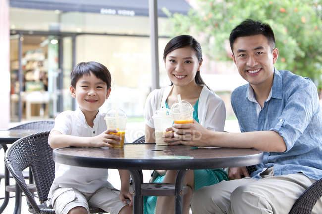 Famiglia cinese seduta nel caffè marciapiede con bevande fredde — Foto stock