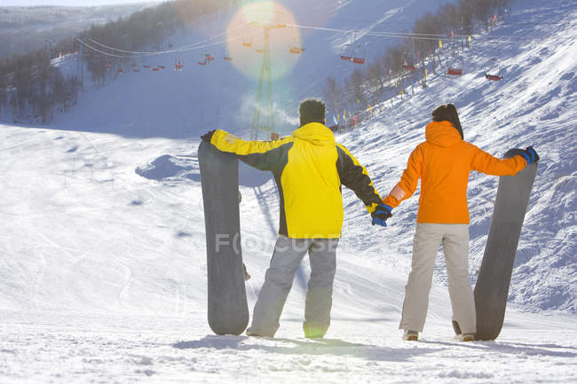 Rear view of young couple with snowboards — Stock Photo