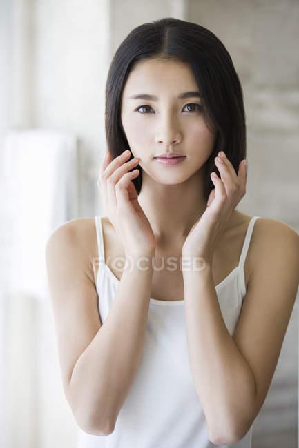 Retrato de hermosa mujer china tocando la cara - foto de stock