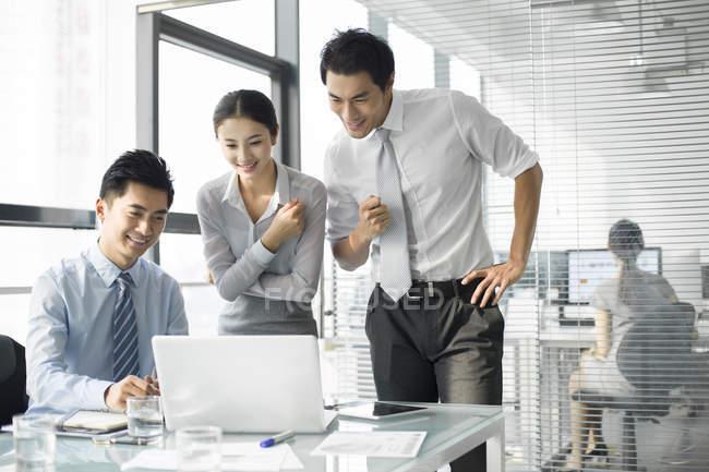 Китайская команда бизнесменов использует ноутбук в офисе — стоковое фото