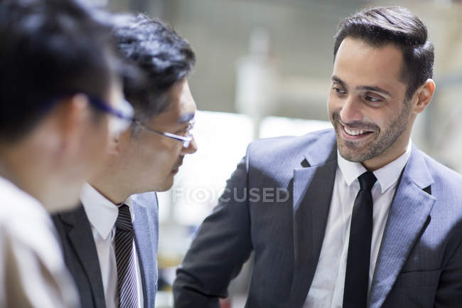 Businessmen and engineers talking at factory — Stock Photo