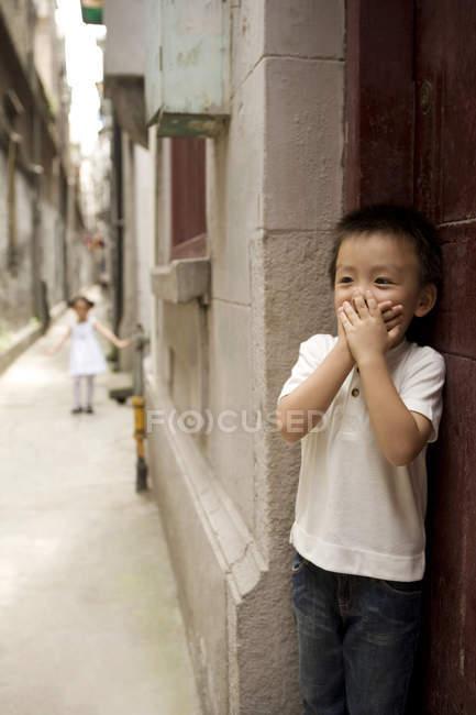 Boca de cobertura menino chinês enquanto brincava de esconder e procurar — Fotografia de Stock