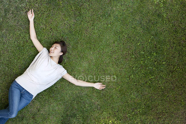 Молодая китаянка лежит на траве с распростертыми руками — стоковое фото