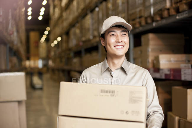 Male Chinese warehouse worker carrying boxes — Stock Photo