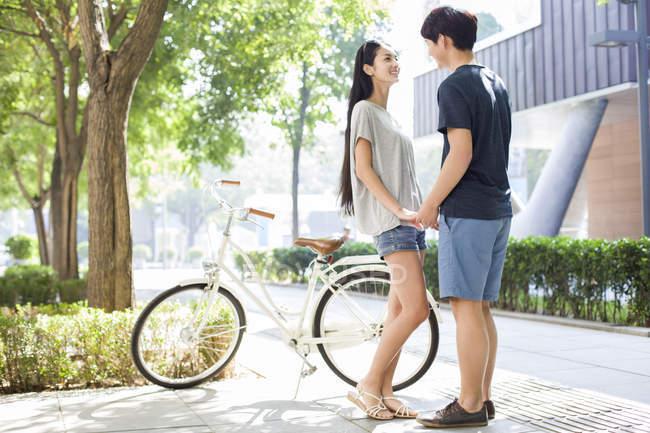 Китайська пара, тримаючись за руки на кампуса з велосипеда — стокове фото