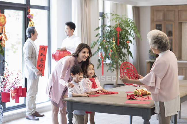 Grandmother with children and mother making Chinese New Year paper-cut — Stock Photo