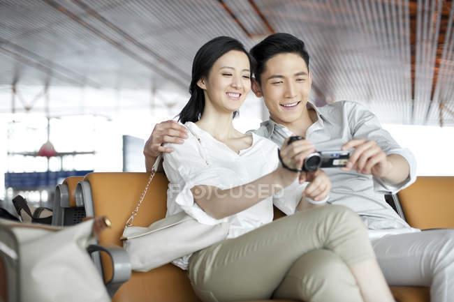 Chinesisches Paar sitzt mit Digitalkamera in Flughafen-Lounge — Stockfoto