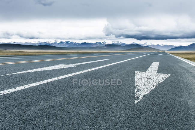 Arrow signs on road in mountains of Tibet, China — Stock Photo