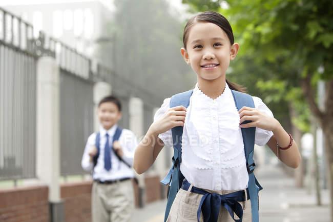 Écolière joyeux avec ses condisciples posant sur la rue — Photo de stock