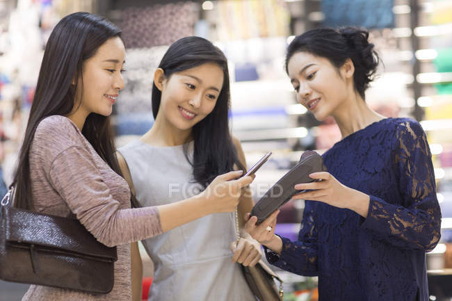 Chinese friends paying with smartphone in clothing store — Stock Photo